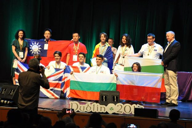 Winning contestants at IOL 2017 being photographed with their medals and country flags